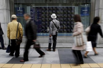 Pedestrians look at an electronic board showing the various stock prices outside a brokerage in Tokyo April 9, 2015. REUTERS/Yuya Shino